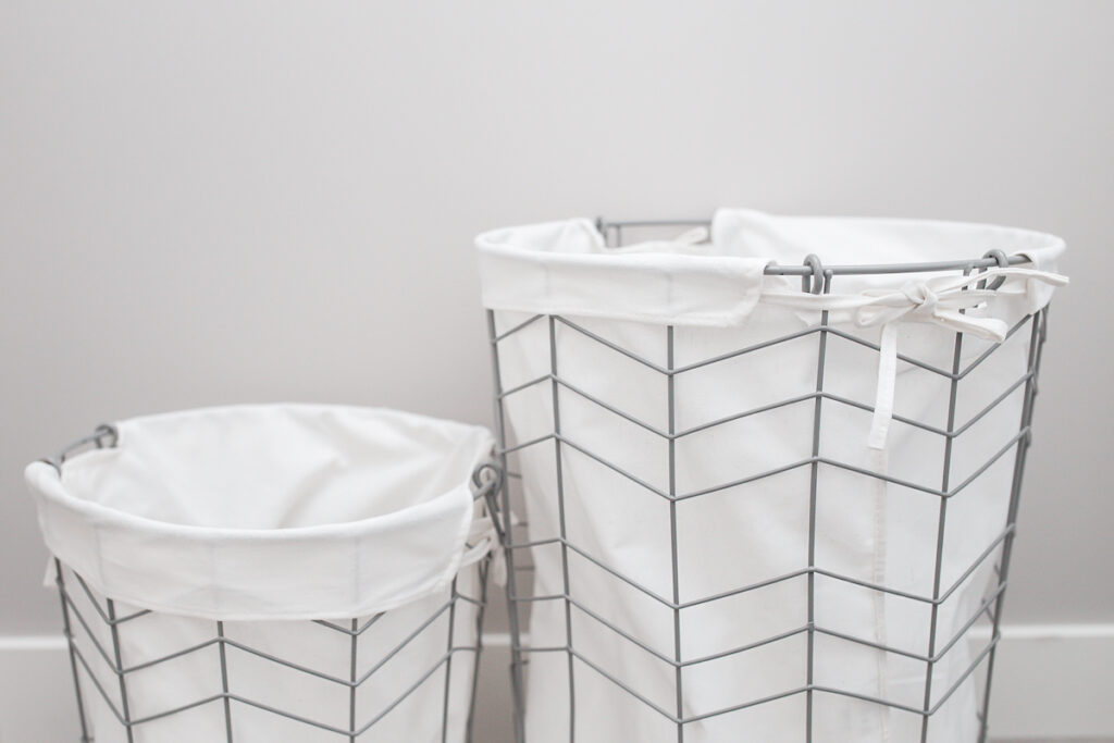 metal laundry hampers with white cloth liners against gray wall