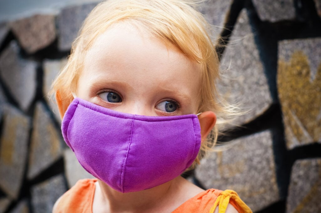 young girl wearing purple cloth face mask