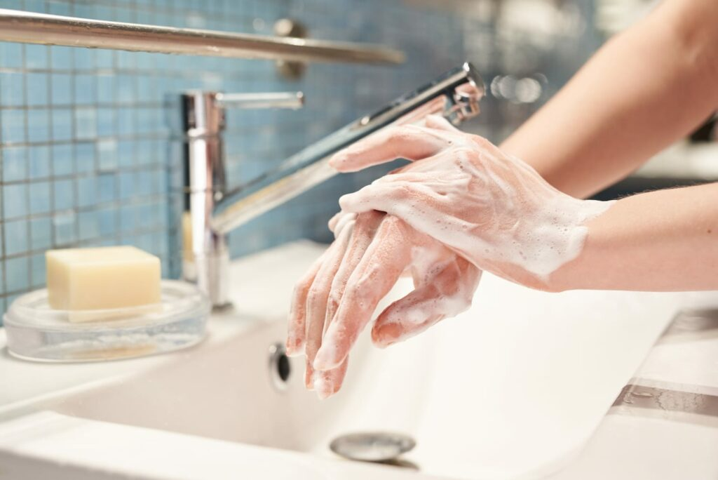womans hands covered in soap at bathroom sink