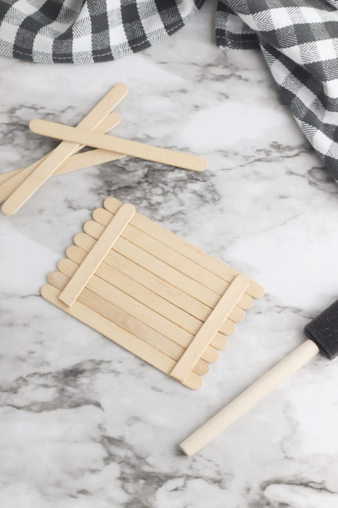 wooden popsicle sticks glued together on a marble table