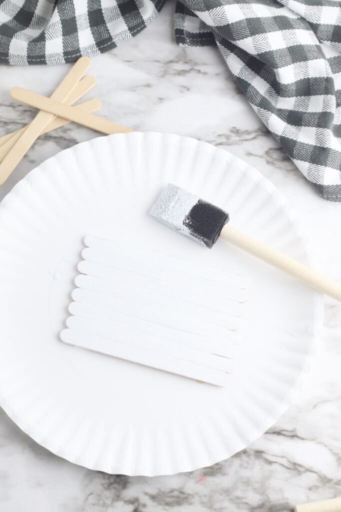 paper plate with popsicle sticks coaster painted white and paint brush nearby