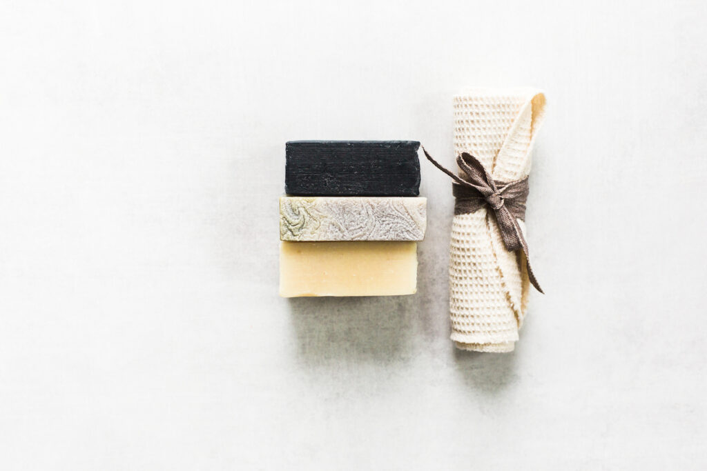 stack of three soaps and rolled washcloth on white marble background