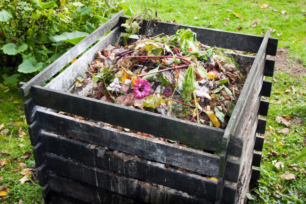 wooden compost bin filled with trash