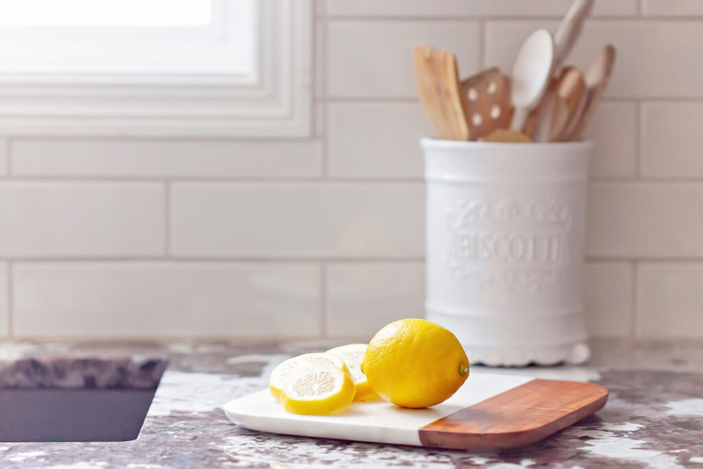lemons on cutting board on marble countertop with kitchen gadgets in jar in background