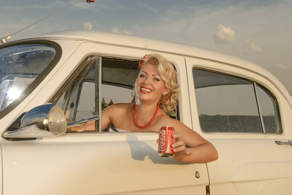 old fashioned woman sitting in retro car holding a can of Coca Cola
