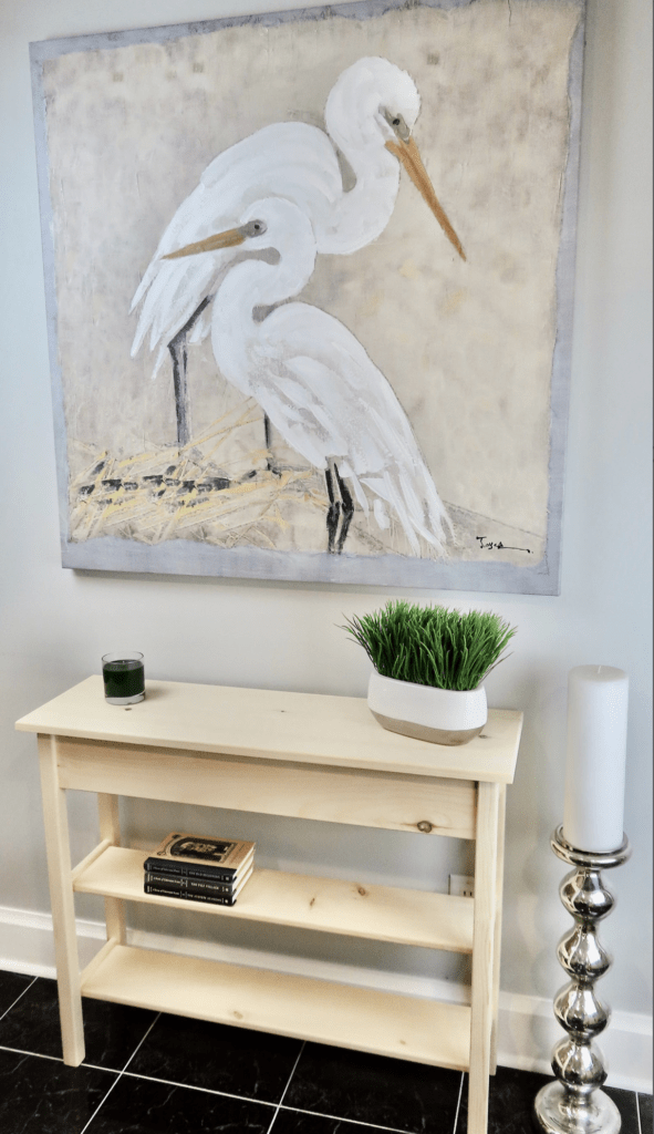 solid wood table with a large painting on wall above