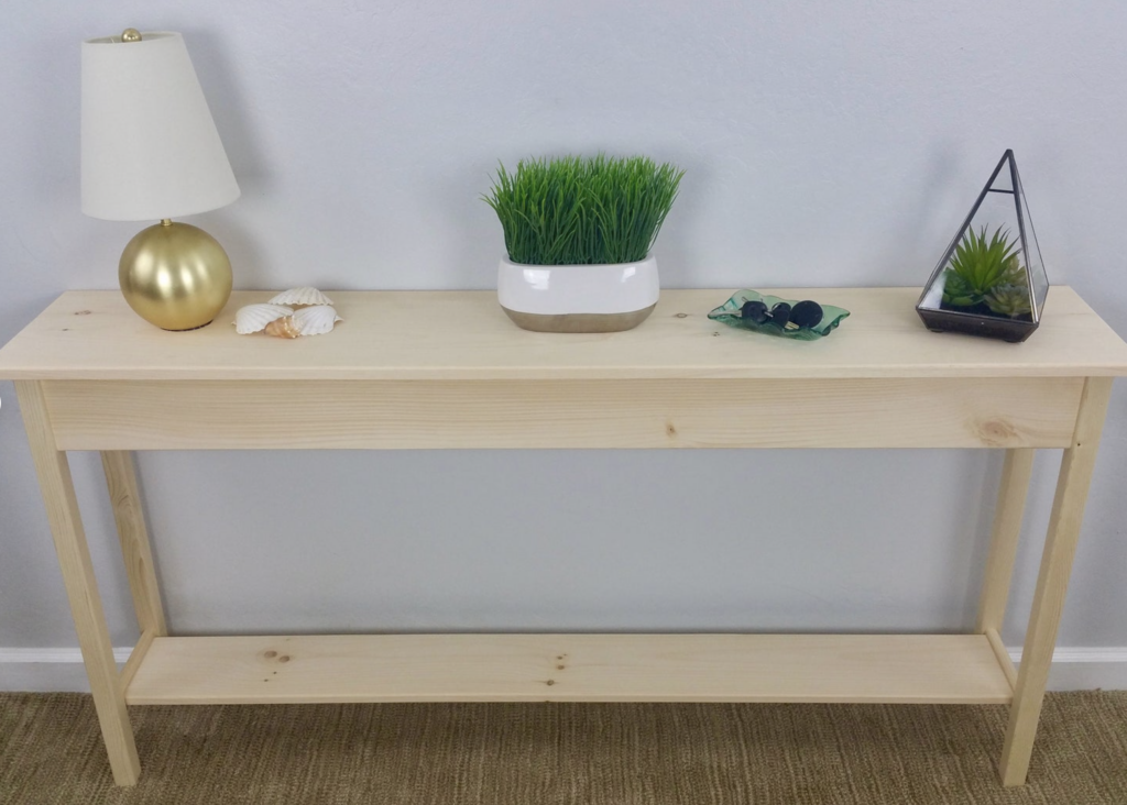unfinished wood table with lamp and plant on top