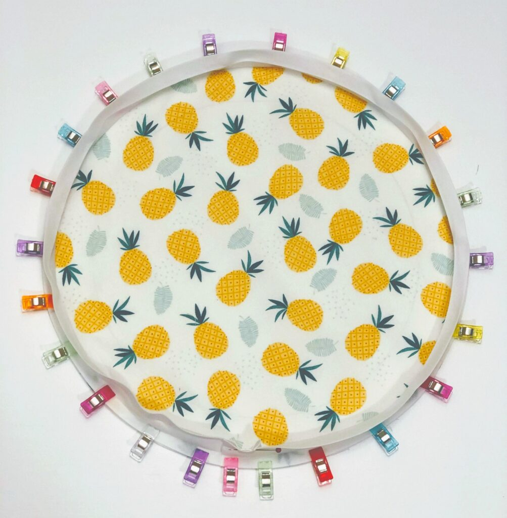 pineapple fabric circle with clips around edges securing bias tape