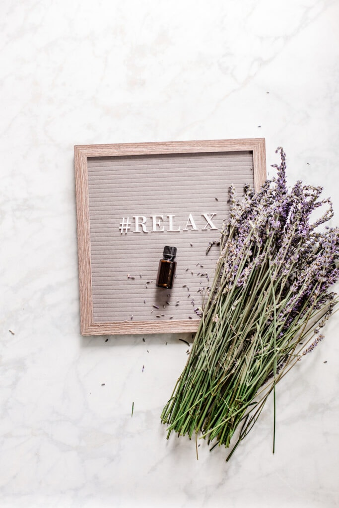 bunch of lavender flowers on top of letter board with word relax