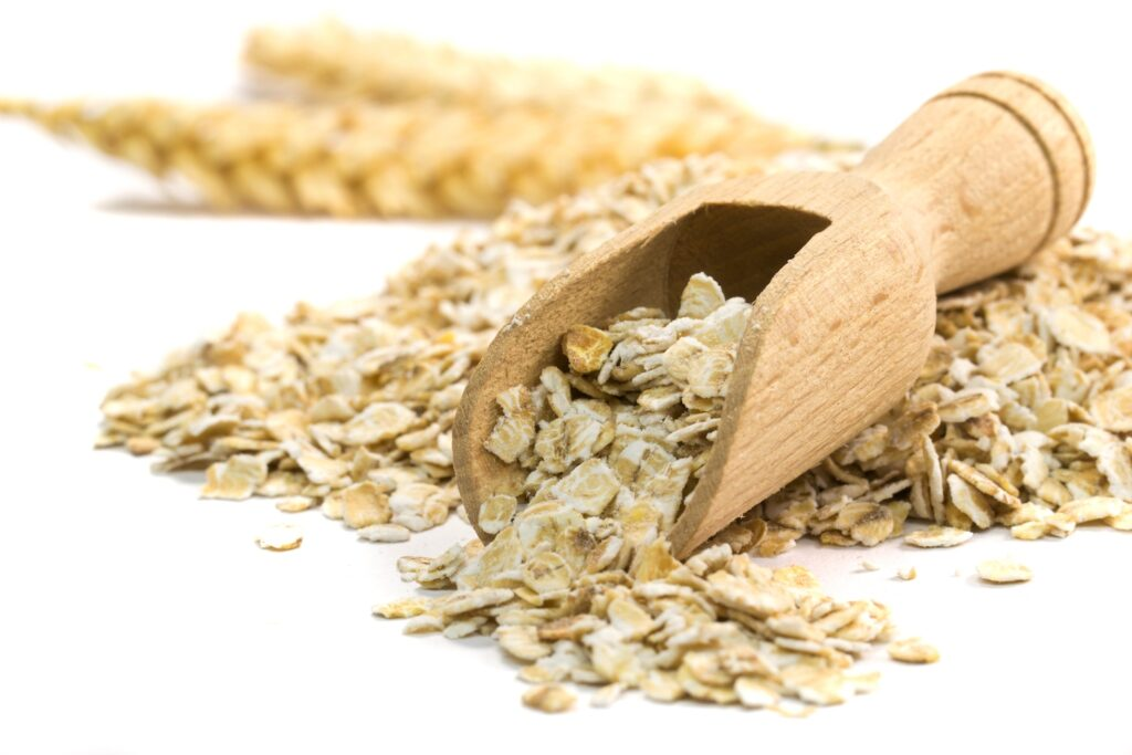 wooden spoon with oatmeal flakes against white background