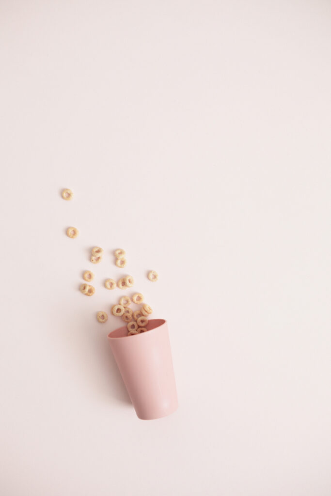 pink plastic cup with cheerios spilling out onto pink background
