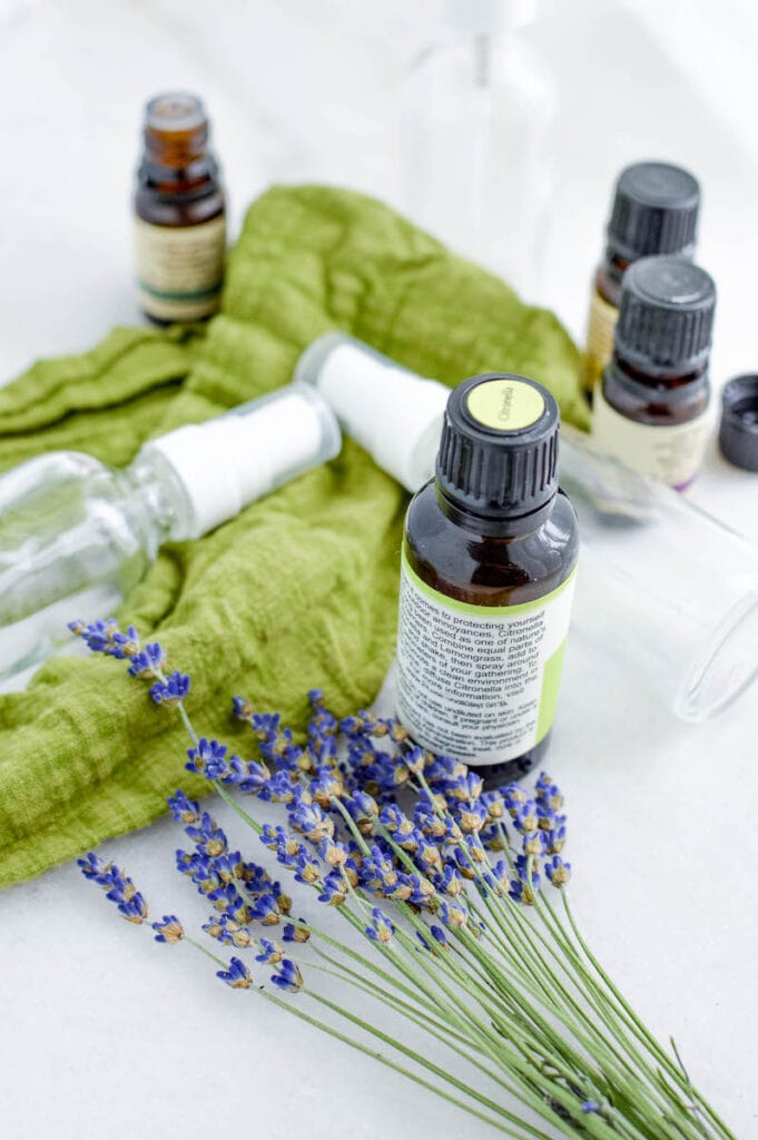 glass spray bottles with essential oils and lavender flowers on green fabric