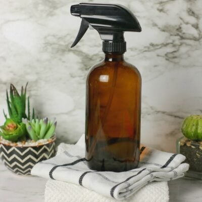 brown spray bottle on top of cleaning rags