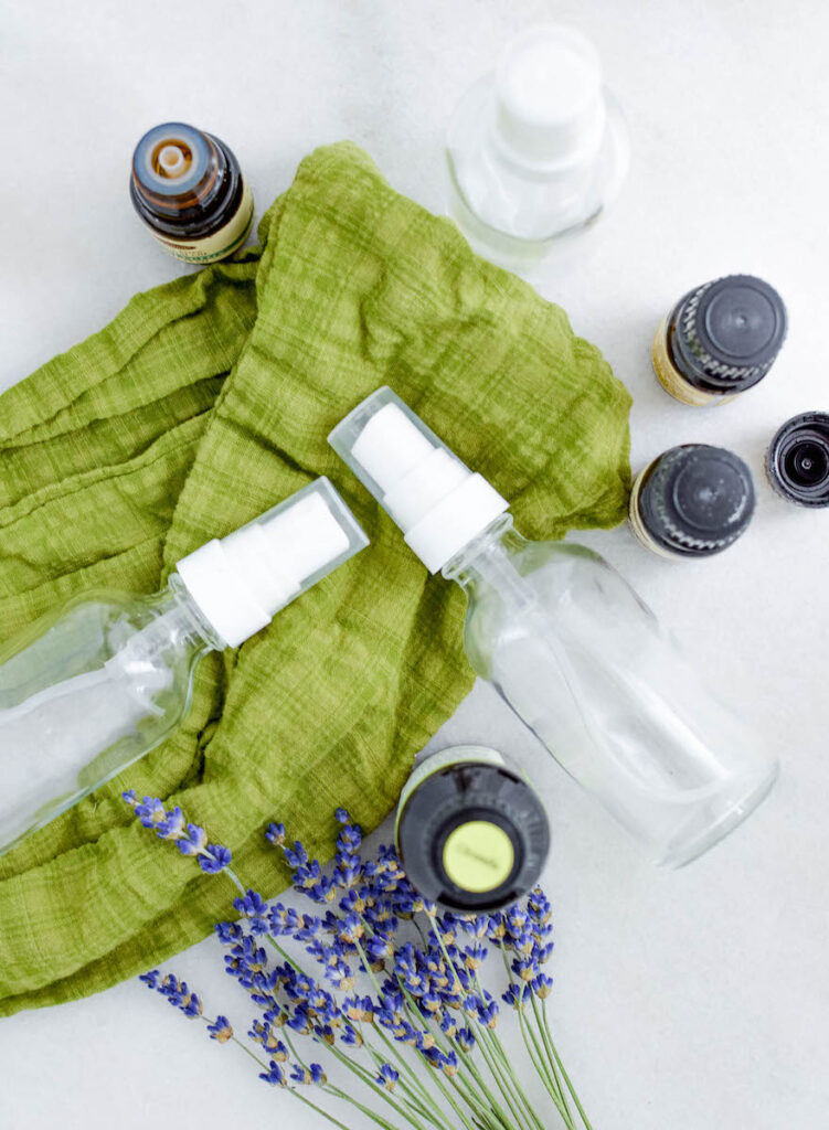 glass bottles and essential oil bottles on green scarf background