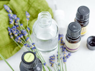 glass bottle and essential oil bottles with lavender flowers