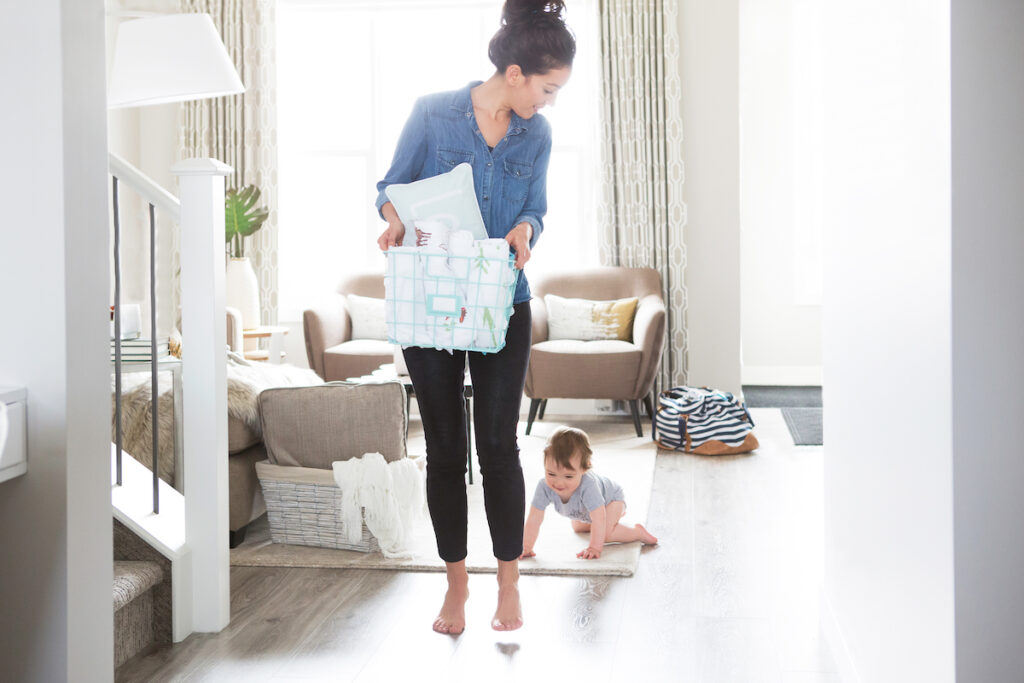 mom carrying laundry basket and baby crawling on floor