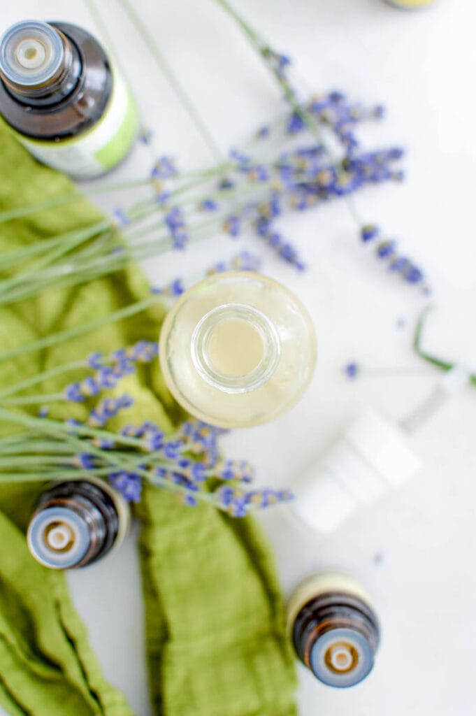 overhead view of glass bottle with essential oils on table