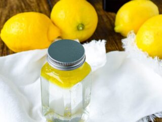 glass bottle filled with vinegar and olive oil sitting on white rag
