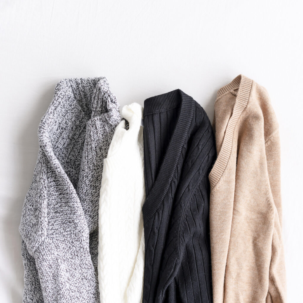 four sweaters on white background