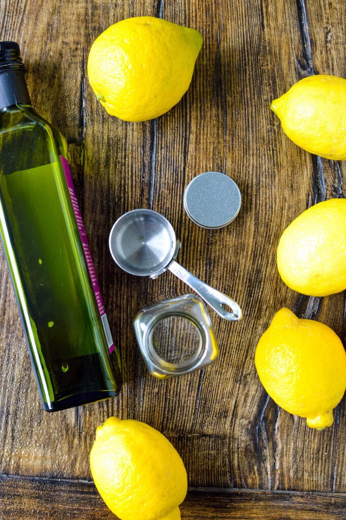 olive oil bottle measuring cups and lemons on wood table
