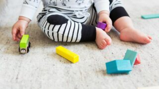 baby on carpet playing with colorful blocks