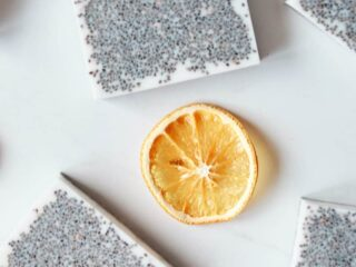 chia seed goat milk melt and pour base soaps on white background with orange slices