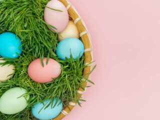 colorful Easter eggs in grass in basket with pink background