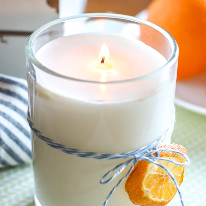 handmade candle with dehydrated orange tied to glass jar