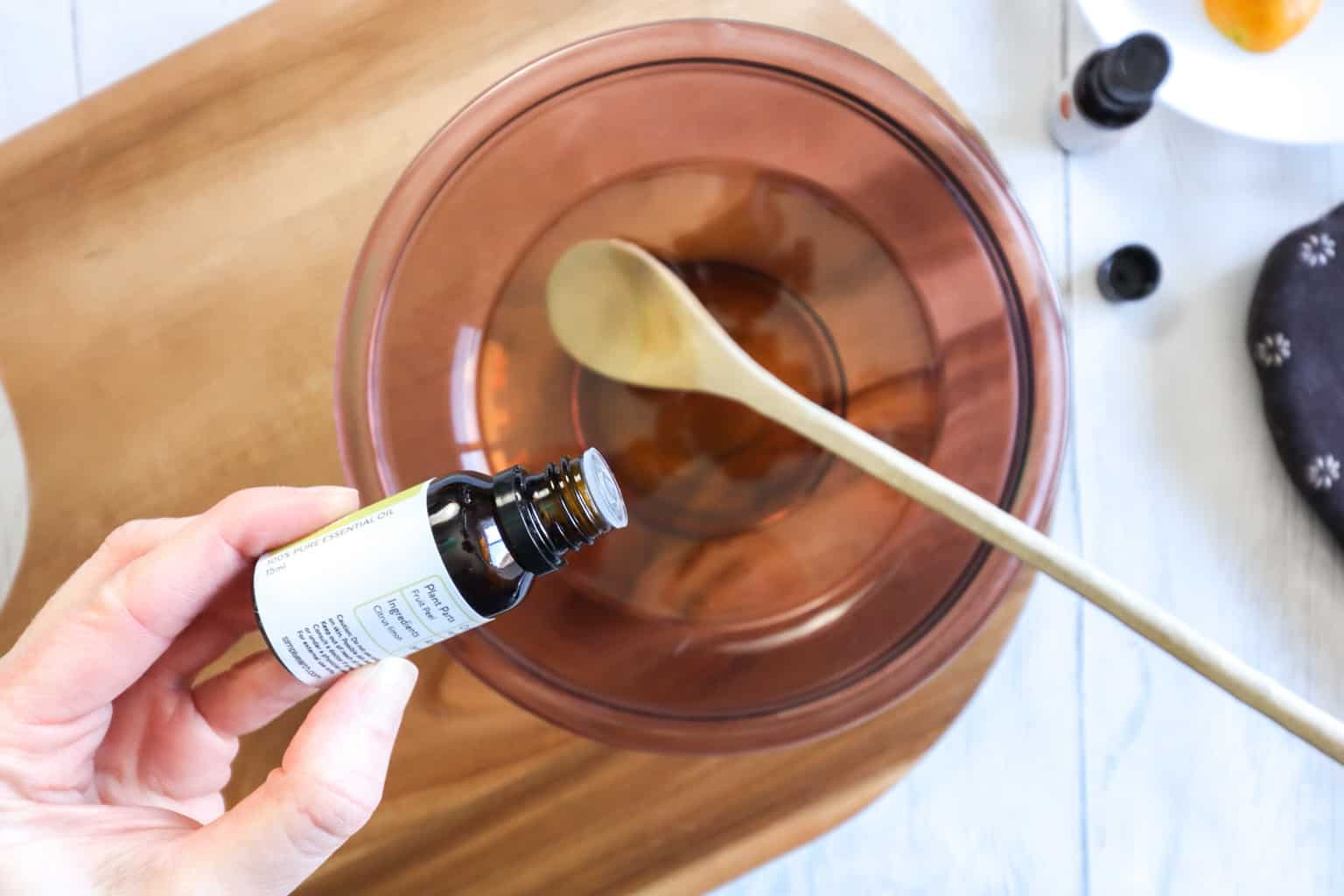 adding essential oils into a bowl of melted candle wax