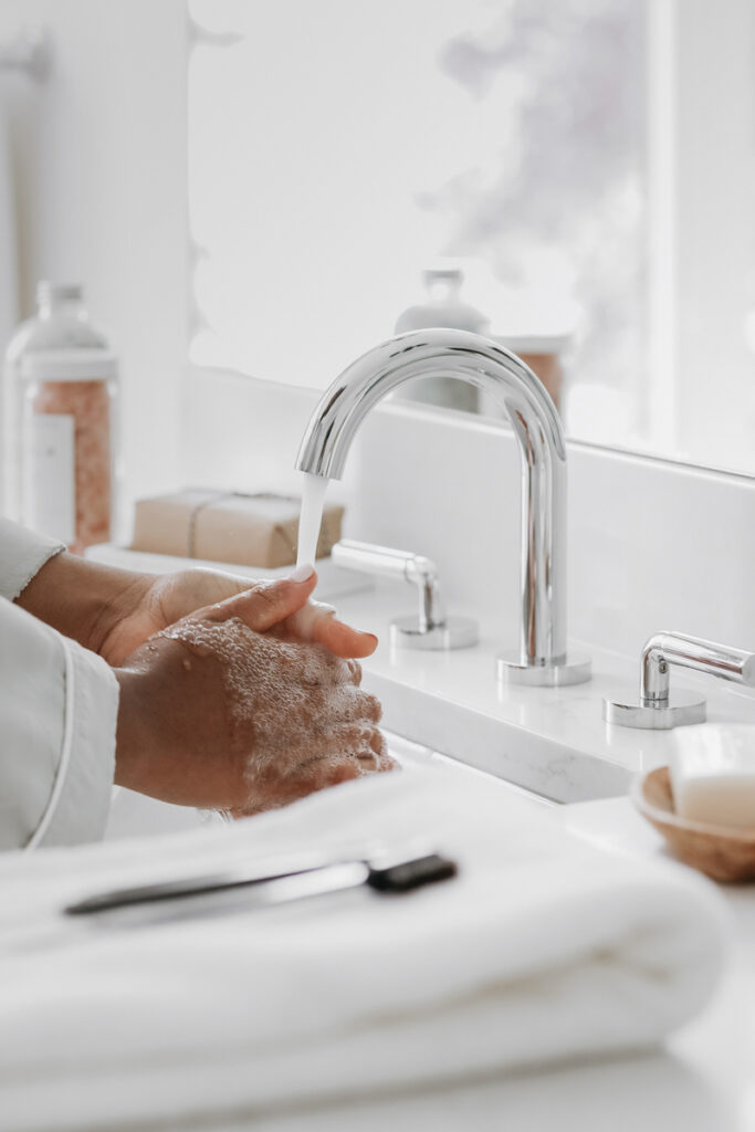 woman washing hands under sink faucet