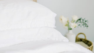 white sheets on a bed with flowers on a bedside table