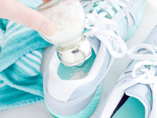 shaking natural foot powder into a smelly shoe